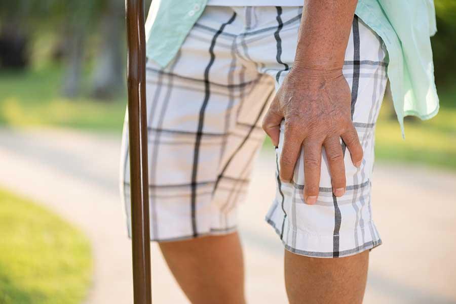 elderly man struggling with osteoarthritis knee pain on his walk