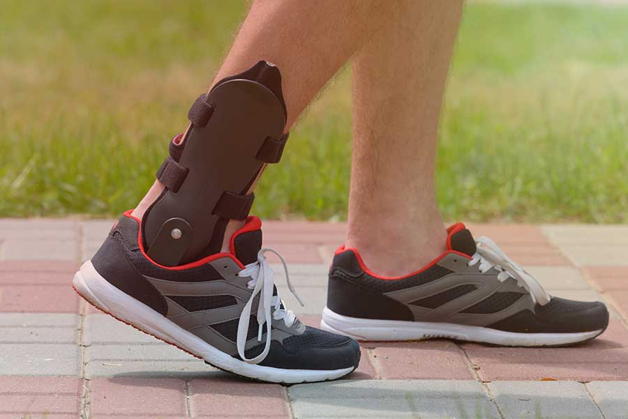 man wearing brace for sprained ankle treatment