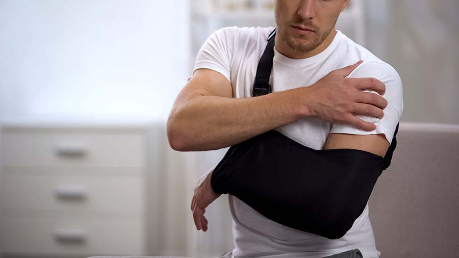 man with arm sling grabing shoudler in pain