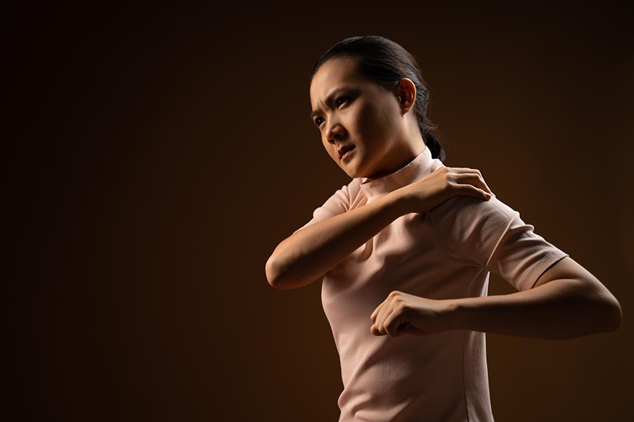 woman performing stretching in shoulder pain physio session