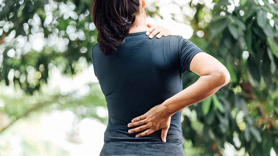 Lady suffering from upper and lower back pain