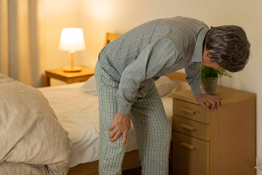 elderly holding knee pain when standing up from bed