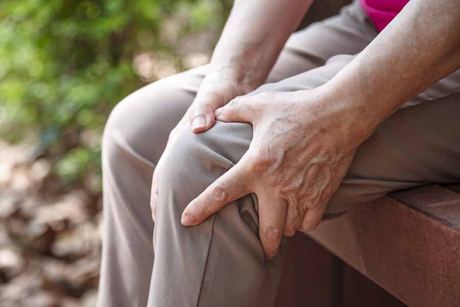 holding knee after walking in the park due to knee instability