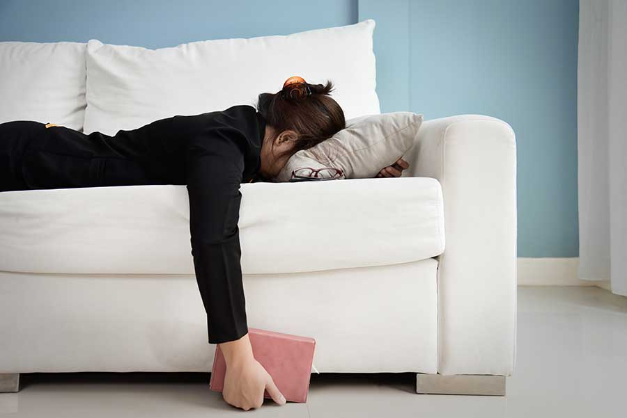 lady exhausted from both work and excercise crashing onto sofa