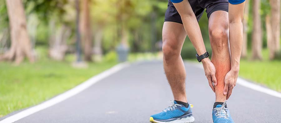 Man holding red shin in pain while running